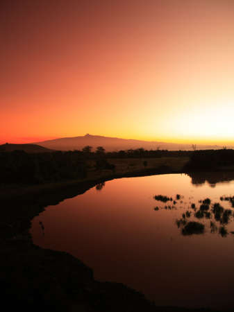 treetops: Mount Kenya sunrise from Treetops waterhole Stock Photo