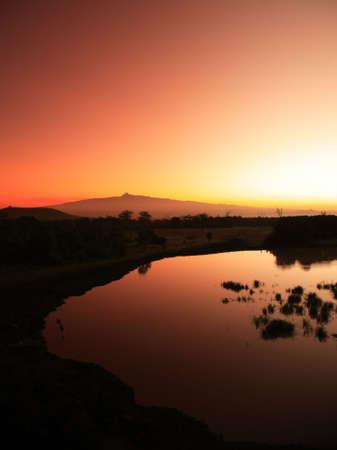 Mount Kenya sunrise from Treetops waterhole Stock Photo