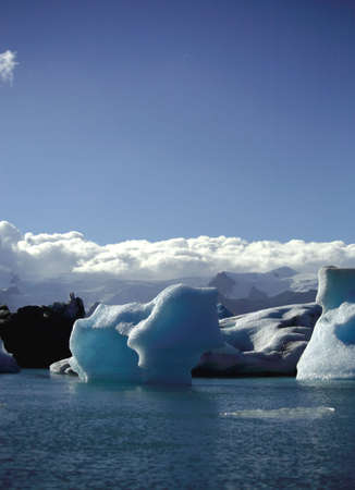 Icebergs against a blue sky and fluffy white clouds  photo