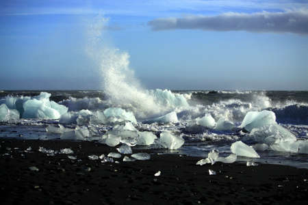 Waves breaking up the icebergs on the beach Iceland photo