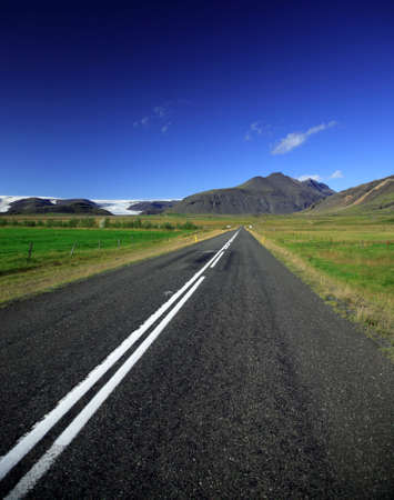 Straight road to the glacier against a bright blue sky Iceland Stock Photo