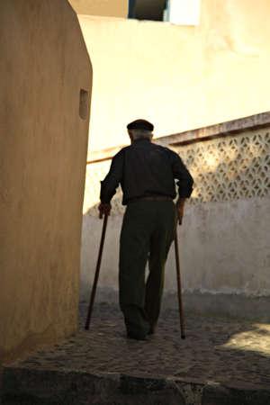 Old man using walking sticks to walk through the streets of Santorini Greece