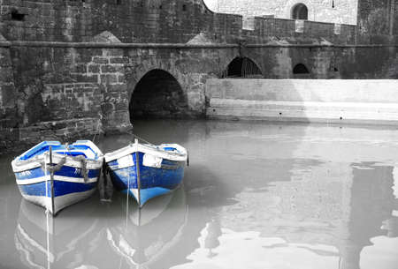 Black and white harbour with two blue boats Essaouria Morocco photo