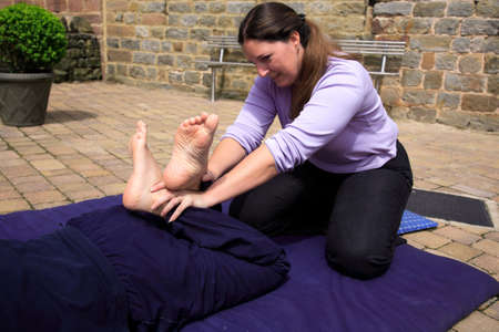 Stretching the quads as part of a Thai body massage photo