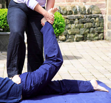 Stretching the lower back as part of a Thai body massage photo