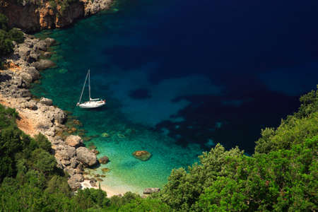 Stunning beach Kefalonia with a sailing boat moored up