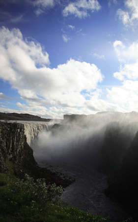 Man looking over the powerful Dettifoss waterfall photo