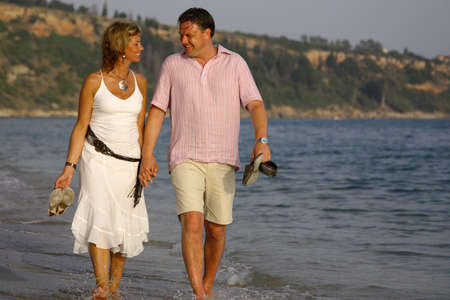 Romantic couple strolling down the beach holding hands Kefalonia Greece