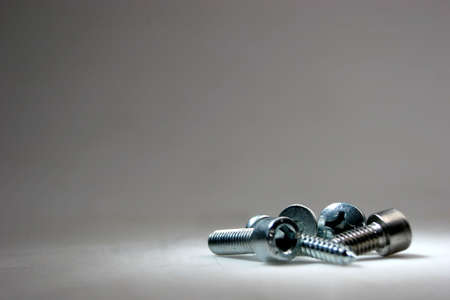 Screws on a grey background Stock Photo