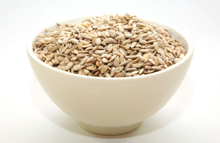 A bowl full of sunflower seeds on a white background photo