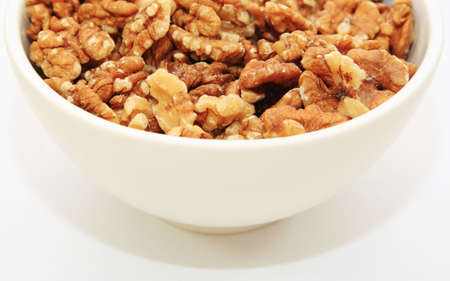 lowering: Half a bowl of walnuts on a white background