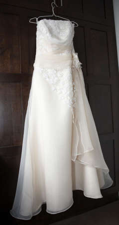 Wedding dress hung up on the wardrobe door Stock Photo