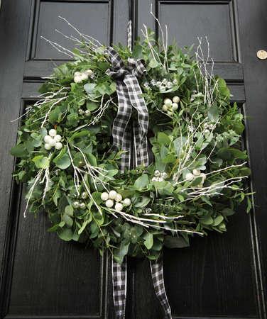 Eucalyptus Christmas wreath hung on a black door photo