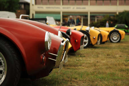 racing car: Red and yellow sports cars lined up at a car show in the UK