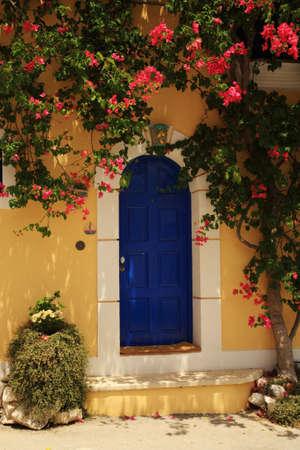 Bougainvillea growing around the door Kefalonia Greece