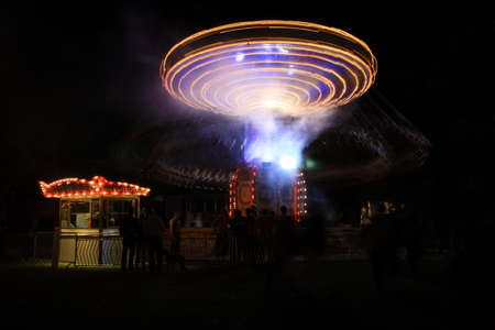 fun fair: Spinning carousel at a fun fair at night in the UK
