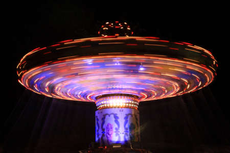Blue and red spinning carousel at night in the UK photo