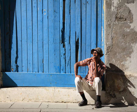Cuban man and his cigar sat on a step in the streets of Havana in Cuba 10 January 2009 Stock Photo - 8559058