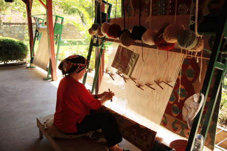 wool rugs: Woman weaving a Turkish rug in Turkey 26 June 2008