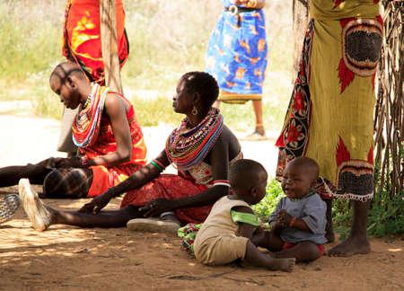Samburu children playing on the floor next tot their mother Samburu village Kenya 20 Janaury 2007