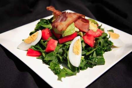 Summer bacon and spinach salad on a white plate, shot with a shallow depth of field photo