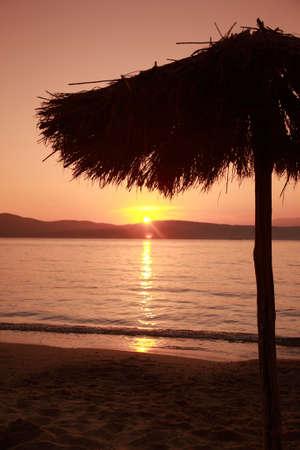 ag: Parasol sunset, Ag Paraskevi beach, Skiathos, Greece Stock Photo