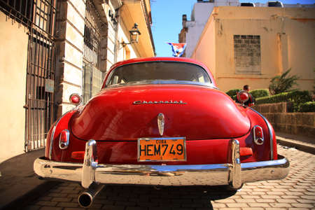 Havana, Cuba - January 13, 2009 - Classic red Chevrolet parked on the streets of Havana, Cuba with the Cuban flag above flapping in the breeze