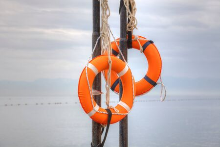 Two life buoys with ropes on a beach photo