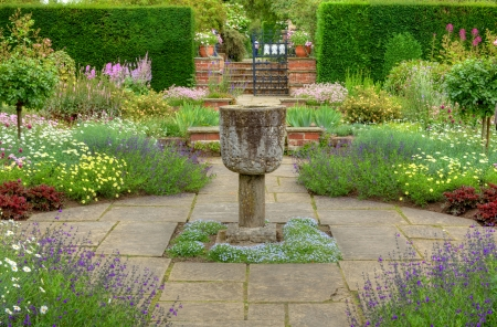 Flagged garden with a stone vase ornament and summer flowers