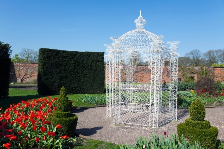 latticework: White wrought iron arbour in an English garden with flowers and topiary shrubs.