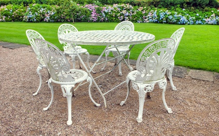 Wrought iron table and six chairs in an English garden  photo