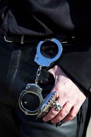 trouser: Handcuffs hanging on a belt of leather trouser man who is also wearing Gothic rings.Handcuffs hanging on a belt of leather trouser man who is also wearing Gothic rings. Stock Photo