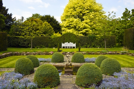Formal English garden with topiary shrubs and stone ornament by the pond