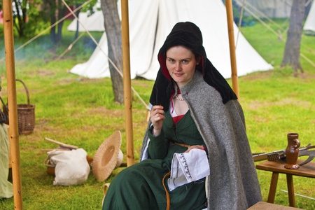 fayre: Young beautiful woman in a medieval costume sewing at Medieval Fayre in tatton Park, Cheshire, England