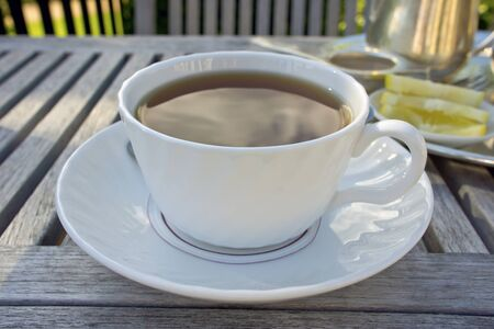 Cup of black tea served on wooden table in a garden  photo