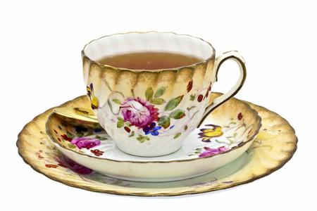 Thee in een antieke porseleinen kop met schotel en dessertbord