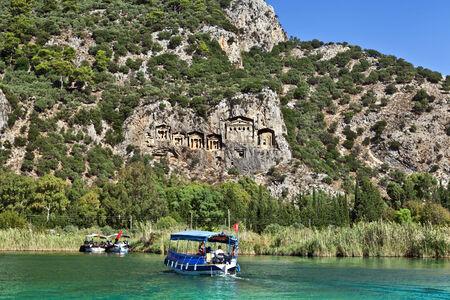 Tourist boats by the historic Kaunian rock tombs in Dalyan, Ortaca, TURKEY.
