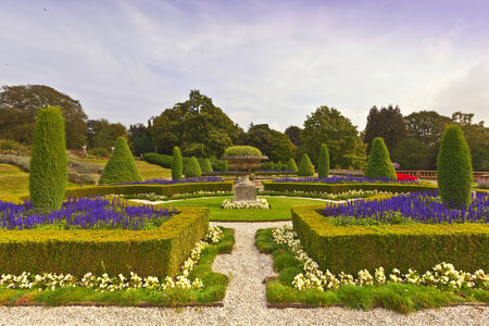 stately: Landscaped garden with topiary and an old stone vase at an historic English estate