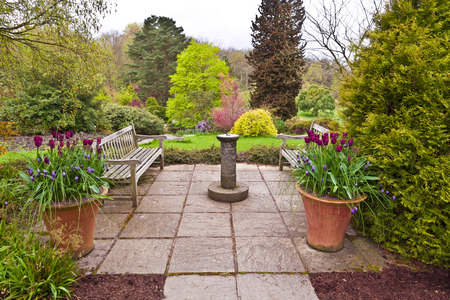 English flagged garden with sundial and tulips in terracotta planters in early spring. photo