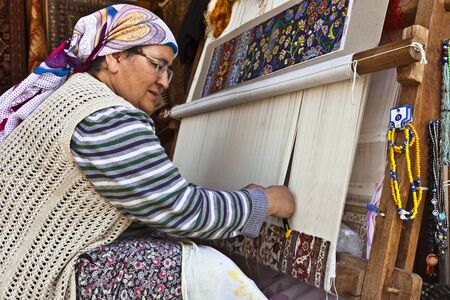 knotting: SIDE, TURKEY - MARCH 9, 2015: Unidentified female weaver knotting a handmade carpet at the shopping area in the town of Side. Editorial