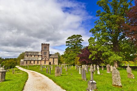 graveyard: Countryside view with old road through graveyard to a rural English church. Stock Photo