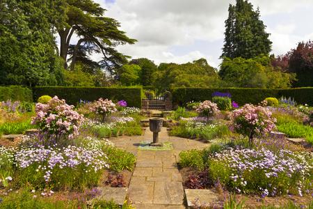 show garden: Corner of a flagged English garden with stone vase.