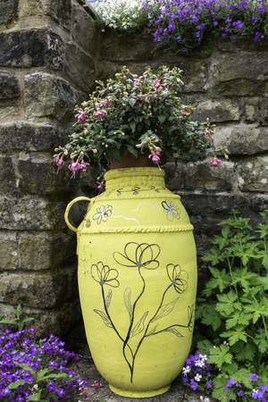urn: Old decorated urn with planted flowers in a garden against stone wall. Stock Photo