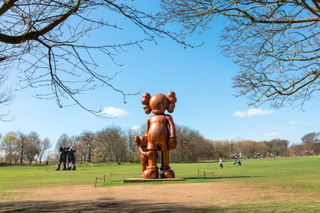 renowned: WAKEFIELD, YORKSHIRE, UK APRIL  19TH 2016: Sculptures by the renowned American artist KAWS exhibited at the Yorkshire Sculpture Park.