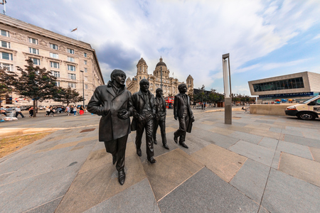 john lennon: LIVERPOOL, UK - AUGUST 18, 2016:  Bronze statue of the four Liverpool Beatles stands on Liverpool Waterfront by sculptor Andrew Edwards.  Fish eye perspective.