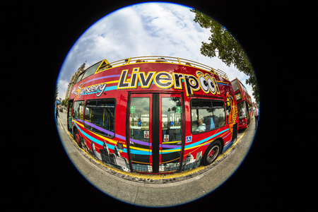 sight seeing: LIVERPOOL, UK - AUGUST 18, 2016: Sight seeing open top bus at the city centre decorated with images of local attractions.  Fish eye perspective.