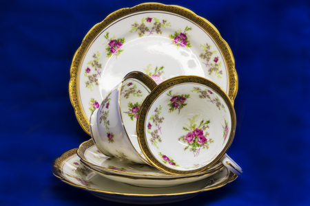 Antique fine china tea cups, saucers and cake plates on blue background.