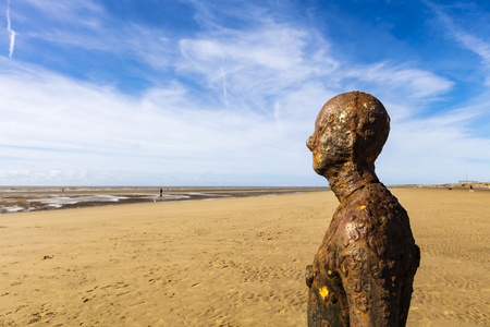 CROSBY BEACH, ENGLAND - SEPTEMBER 13, 2016: Detail of Another Place by Antony Gormley consists of 100 cast-iron, life-size figures spread out along three kilometres of the foreshore near Liverpool.