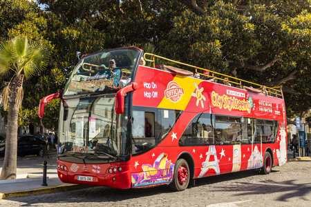 CADIZ, SPAIN - SEPTEMBER 27, 2016: Brightly decorated sightseeing double-decker open top bus in Cadiz takes visitors to all the major tourist attractions.