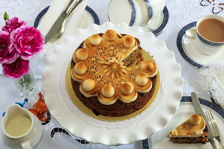 currents: Simnel cake - traditional Easter fruit cake decorated with marzipan on a table set for tea. Stock Photo